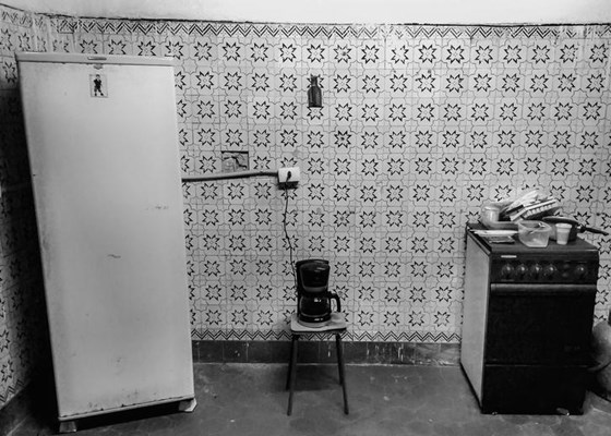 Fridge, kettle and old cooker in a run down and dirty kitchen