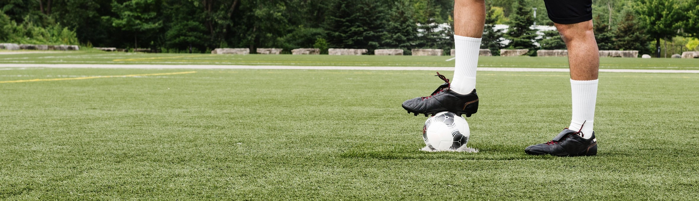 Foot resting on football on a green football pitch