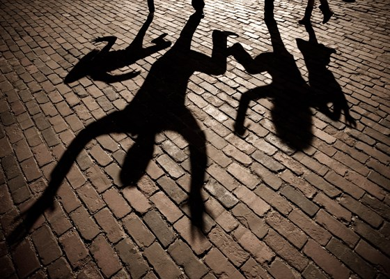 Shadows on brick of family jumping