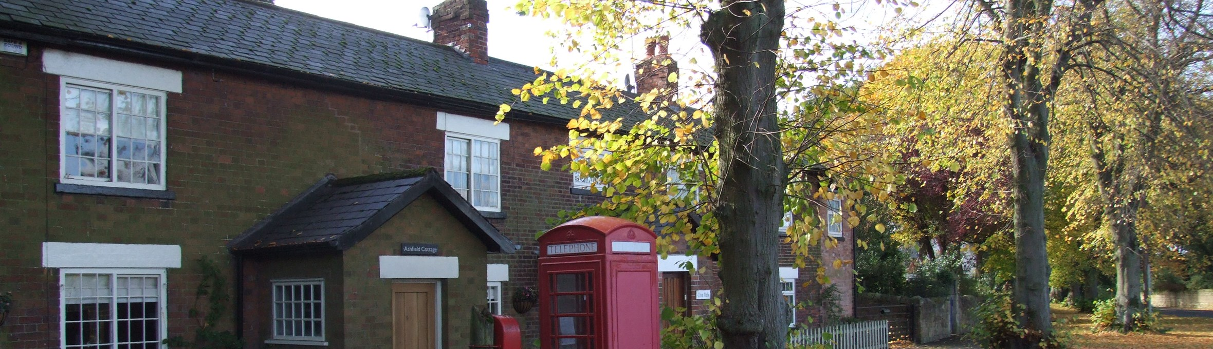 Row of brick cottages under trees with red phone box