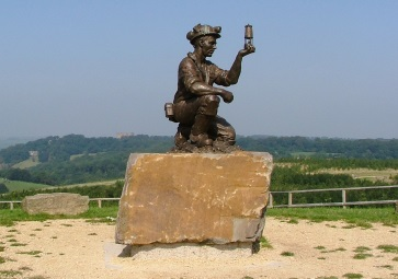 Statue of a miner holding up a Davey lamp, rock plinth, with open view of countryside behind