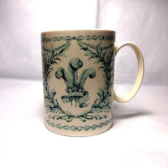 Commemorative mug designed by Carl Toms - green design with royal insignia on cream mug