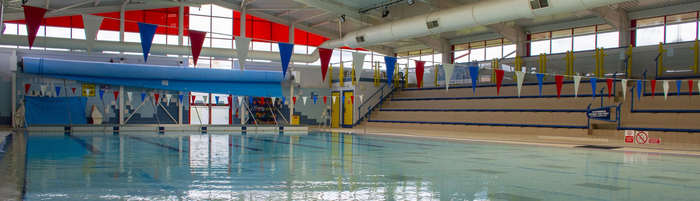 A view of an empty swimming pool with bunting across the roof