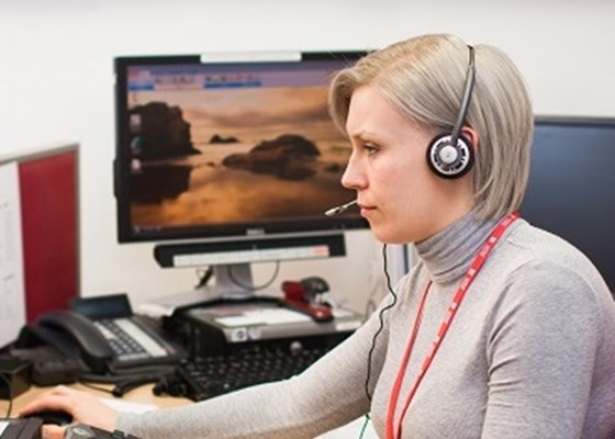 Female Lifeline operator sat in profile at computer with phone headset on