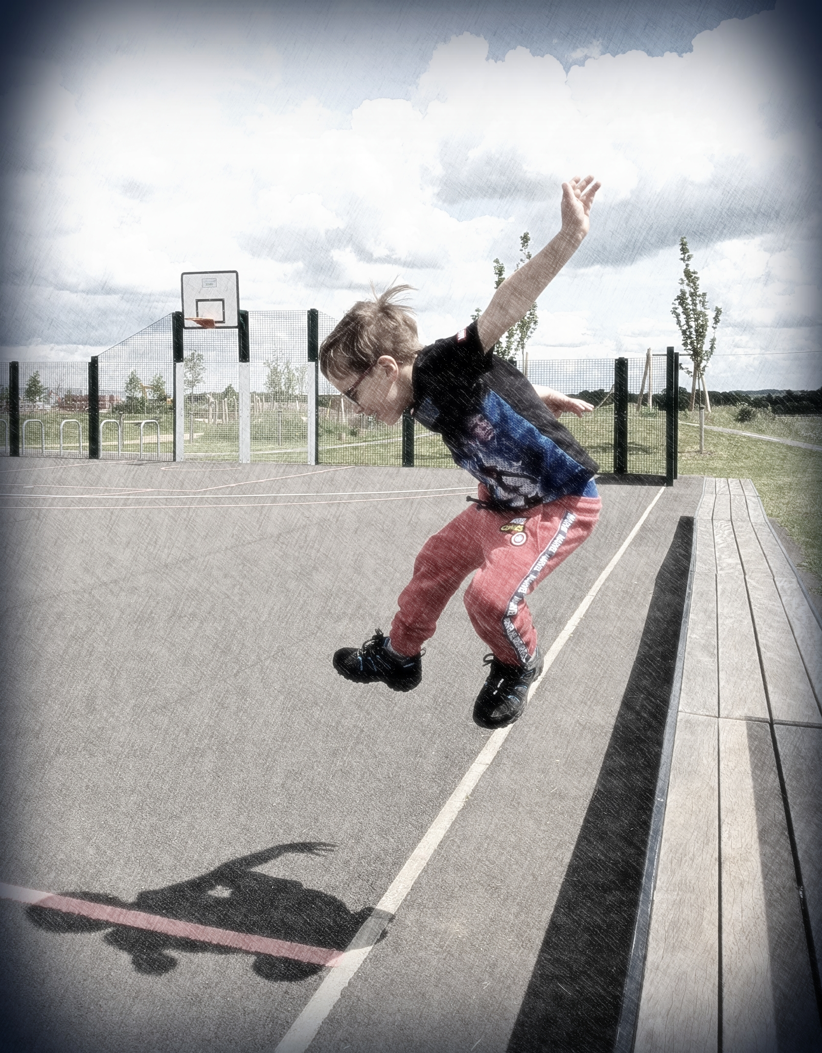 Young child in mid-air jump at a skatepark with shadow on the ground